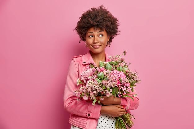 Задумчивая афроамериканка с красивым букетом цветов, одетая в модную одежду,