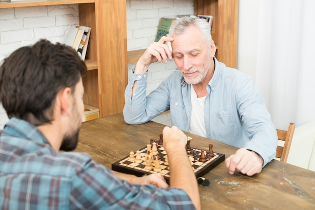 Pensive aged man and young guy playing chess at table near bookshelves