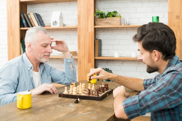 Pensive aged man and young guy playing chess at table in room