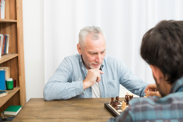 Pensive aged man and young guy playing chess at table