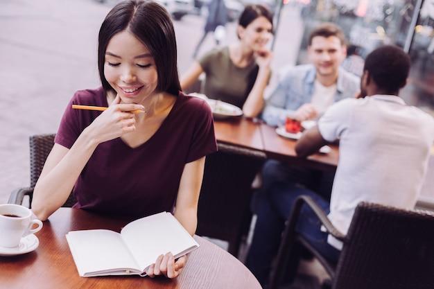 Задумчивая привлекательная студентка смотрит вниз, работая в кафе и держа карандаш