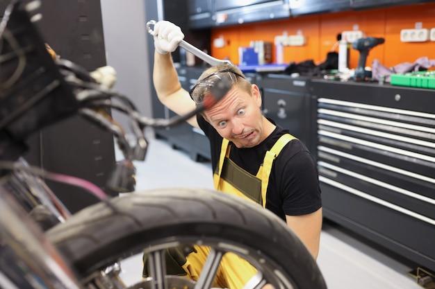 物思いにふける見習い研修生錠前屋は、オートバイのオートバイの修理訓練を修正する方法を考えています