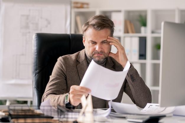 物思いに沈んだ建築家または監督がオフィスの机で仕事に集中しながら紙のスケッチを見て