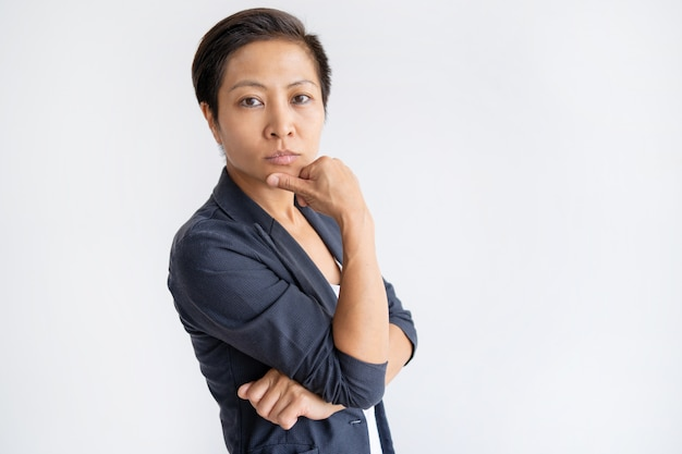 Pensive asian business woman touching chin with fingers