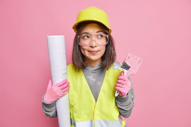 Pensive asian female maintenance worker holds rolled blueprint painting brush looks away thoughtfully wears uniform poses on pink