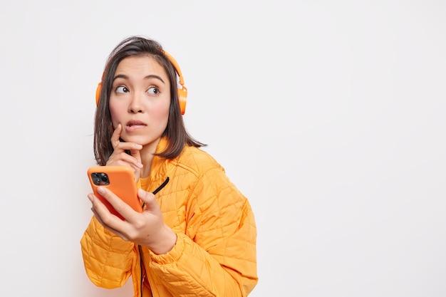 Задумчивая азиатская женщина-модель кусает губы с задумчивым взглядом, использует смартфон и стереонаушники для прослушивания музыки, одетая в куртку, изолированную на белой стене с пустым пространством справа