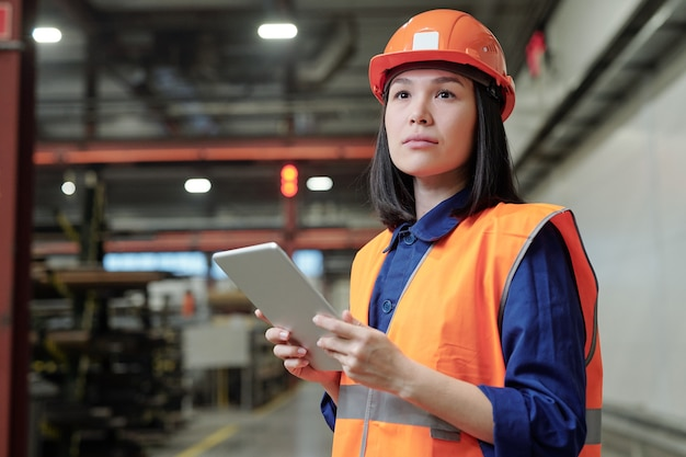 Pensive asian female process engineer in work helmet and safety vest using digital tablet at factory