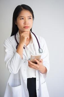 電話を使用している夢中のアジアの医学生