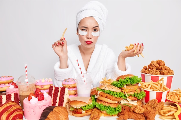 Pensive asian woman focused at camera surrounded by fast food Premium Photo