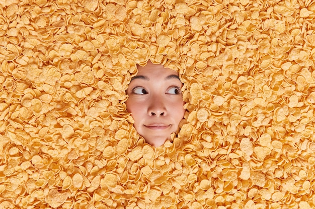 Pensive asian woman looks away with thoughtful expression drowned in dry cornflakes going to have healthy breakfast thinks about something has attentive gaze on right