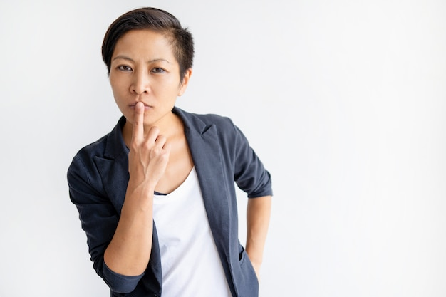 Pensive asian woman touching mouth with finger