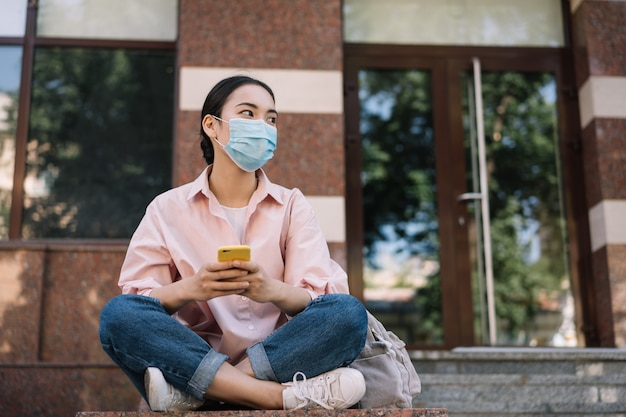 Pensive asian woman wearing medical mask using mobile phone, sitting alone.  social distance concept