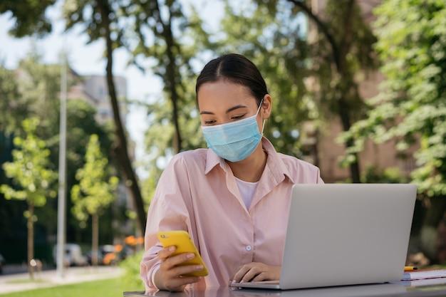 Задумчивая азиатская женщина в медицинской маске с помощью мобильного телефона, работающего онлайн