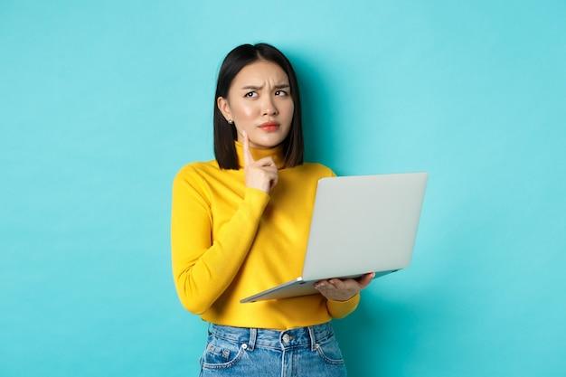 Задумчивая азиатская женщина, работающая на ноутбуке, думая и глядя, принимая решение, стоя на синем фоне.