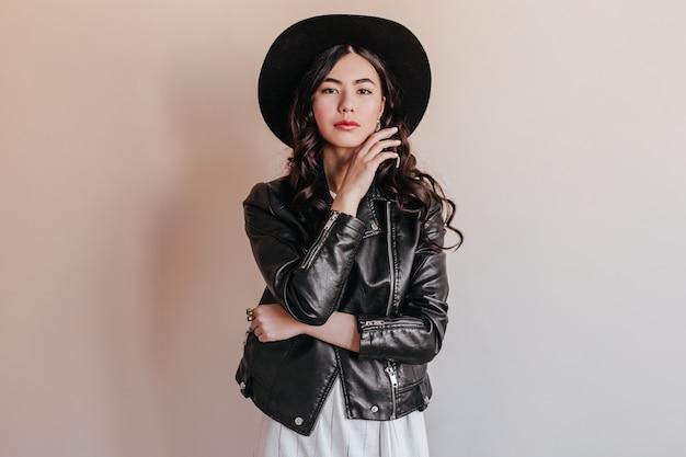 カメラを見て帽子をかぶった物思いにふけるアジアの若い女性。ベージュの背景に立っている革のジャケットの日本人女性。
