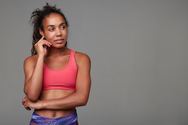 Pensive athletic young dark skinned curly lady with casual hairstyle looking thoughtfully aside and touching her face gently, dressed in sporty wear