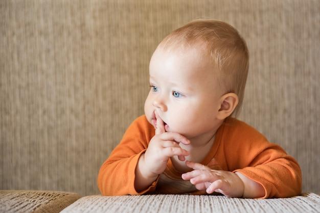 口の中に指で物思いにふける魅力的な男の子