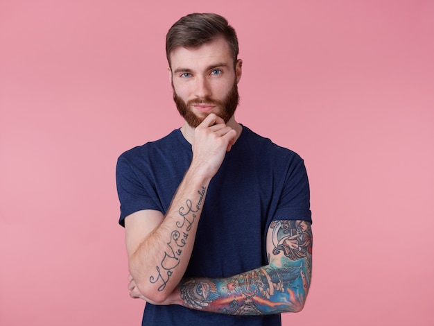 Задумчивый привлекательный рыжебородый парень с голубыми глазами, одетый в синюю футболку, держит руку за подбородок и задумчиво смотрит в камеру, изолированную на розовом фоне.