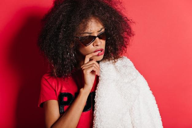 Donna attraente pensierosa con la pelle scura che posa in occhiali da sole