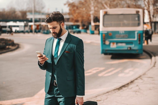 Pensive bearded businessman in turquoise suit holding luggage and using smart phone while waiting for bus. thoughts become things.