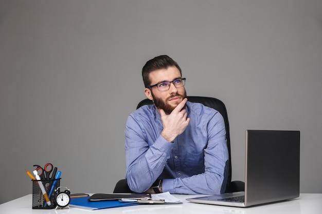 Задумчивый бородатый элегантный мужчина в очках держит подбородок и смотрит вверх, сидя за столом в офисе