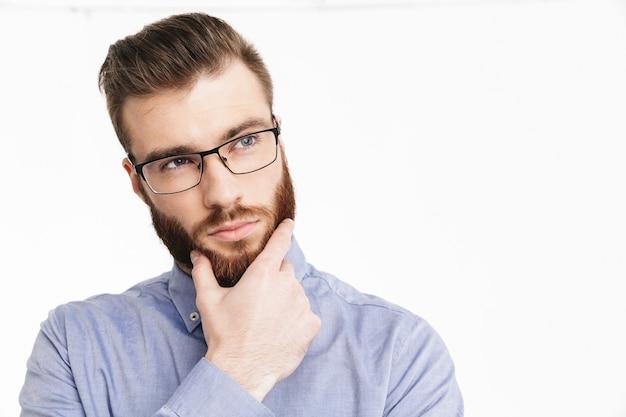 Задумчивый бородатый элегантный мужчина в очках держится за подбородок и смотрит в сторону