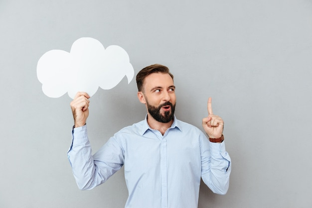 Pensive bearded man in business clothes holding blank speech cloud