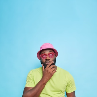 L'uomo barbuto pensieroso tiene il mento concentrato sopra considera che qualcosa prenda una decisione indossa abiti estivi occhiali da sole rosa isolati sul muro blu