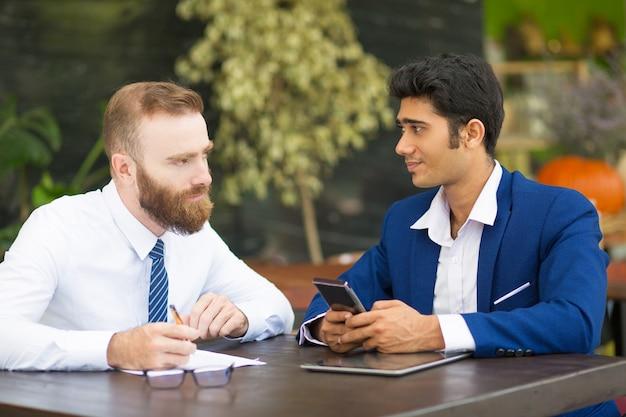 Pensive bearded man talking to business partner in modern cafe