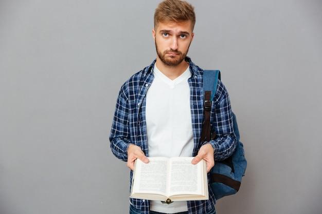 Задумчивый бородатый мужчина с рюкзаком держит открытую книгу с пустыми страницами, изолированными на серой стене
