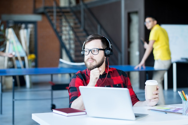 Задумчивый бородатый человек, работающий в офисе