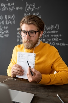 Pensive bearded teacher in yellow pullover thinking of new lecture in front of laptop while having short break between online lessons