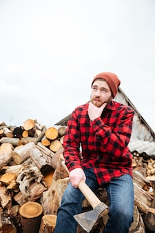 로그에 앉아 생각하고 격자 무늬 셔츠와 모자에 잠겨있는 수염 난 젊은이