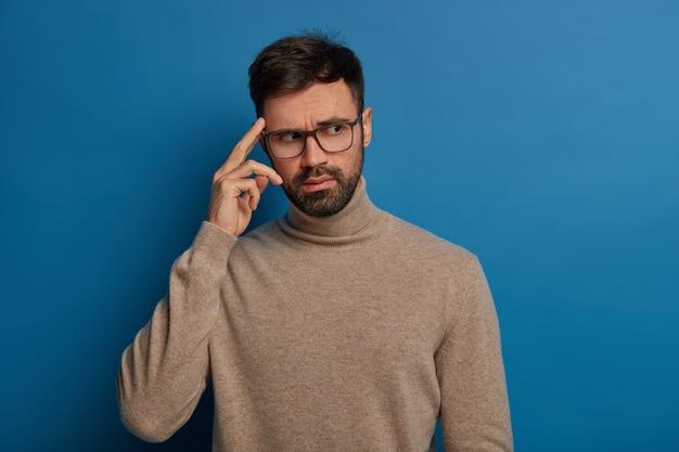 Il giovane barbuto pensieroso tiene il dito sulla tempia, ricorda le informazioni necessarie in mente, indossa occhiali trasparenti e un maglione casual