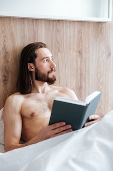 Pensive bearded young man reading book and thinking in bed