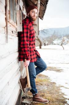 Задумчивый бородатый молодой человек стоит возле старого деревянного дома в деревне и держит топор