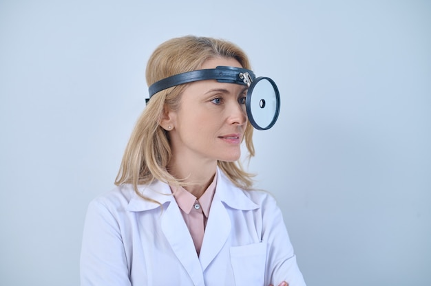 Pensive beautiful blonde middle-aged lady doctor looking away