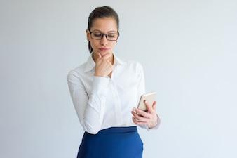 Pensive beautiful businesswoman using smartphone and touching chin.