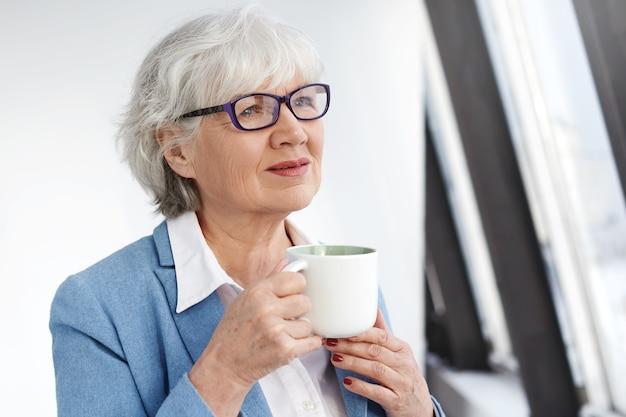 スタイリッシュな長方形の眼鏡とマグカップを持った青いジャケットを着て、新鮮なカプチーノの香りを楽しんでいる物思いにふける美しい女性年金受給者。お茶を飲む白髪のエレガントな年配の女性