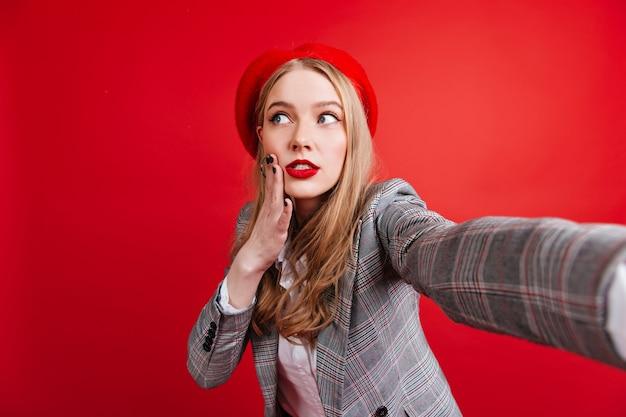 自撮りをしているベレー帽の物思いにふける美しい少女。赤い壁にポーズをとってエレガントなジャケットのかなり若い女性。