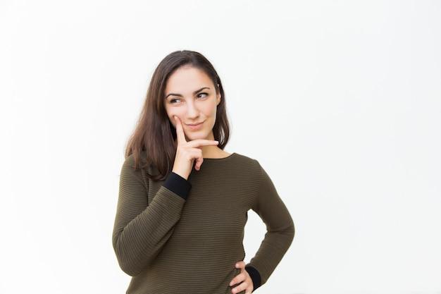 Pensive beautiful woman touching cheek and chin