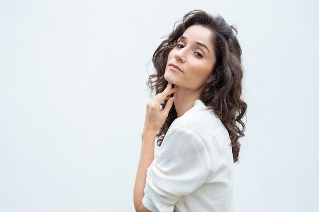 Задумчивая красивая женщина касаясь кожи подбородка и шеи