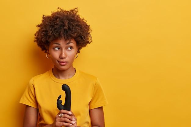 Pensosa bella donna con i capelli afro che esplorerà il potere vibrante del nuovo sex toy, tiene il vibratore per la vagina, stimola il clitoride, usa il massaggiatore su diverse parti del corpo, raggiunge l'orgasmo