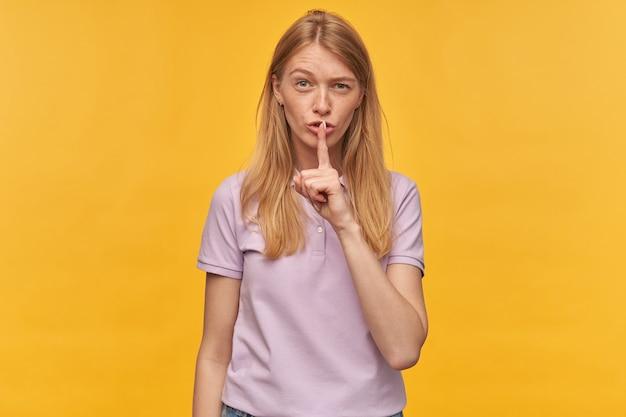 La bella donna pensierosa con le lentiggini in maglietta della lavanda tiene la fronte alzata e mostra il gesto di silenzio sul giallo