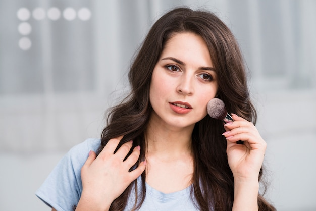 Pensive beautiful woman with makeup brush