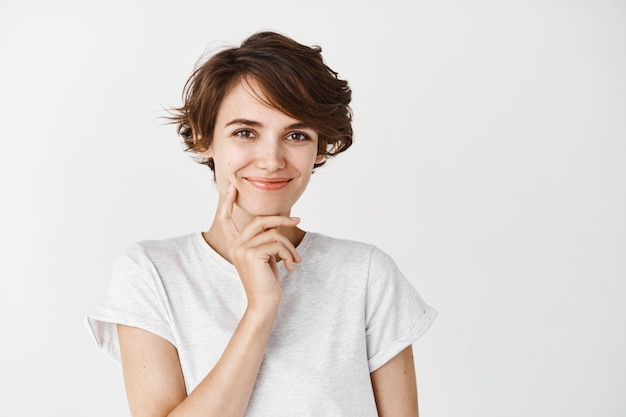 Pensive beautiful woman with short messy hair, smiling and touching clean perfect skin without makeup, standing on white wall
