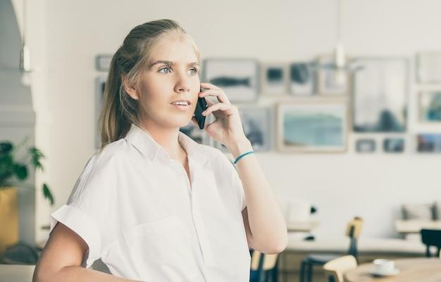 Задумчивая красивая молодая женщина в белой рубашке, разговаривает по мобильному телефону, стоит в коворкинге и смотрит в сторону