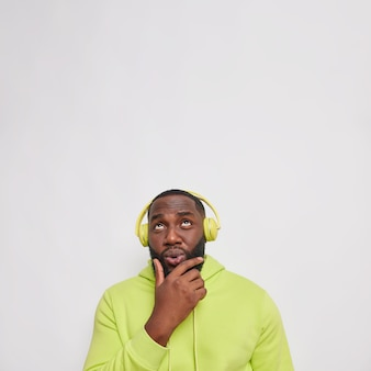 Pensive black bearded man holds chin concentrated above considers something while listens lyrics song in headphones wears sweatshirt keeps head raised up isolated over white wall copy space