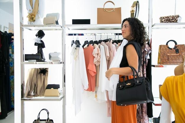 Donna dai capelli neri pensierosa che sceglie i vestiti, si applica la camicetta e si guarda allo specchio. vista laterale. negozio di moda o concetto di vendita al dettaglio