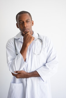 Pensive black male doctor touching chin. Medical decision concept.